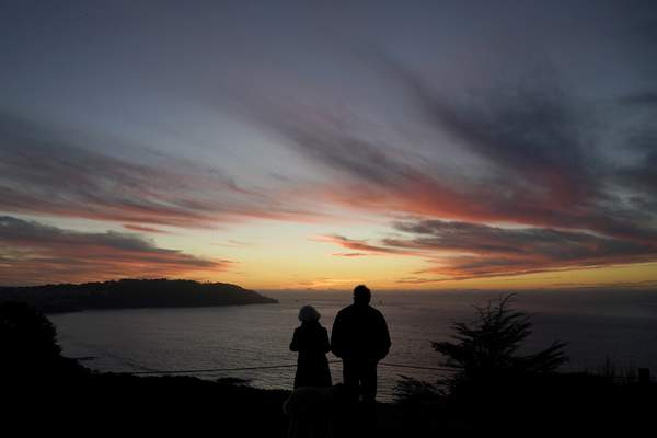 FILE - In this Dec. 21, 2020, file photo people watch as the sun sets from the Presidio in San Francisco. (AP Photo/Jeff Chiu, File)