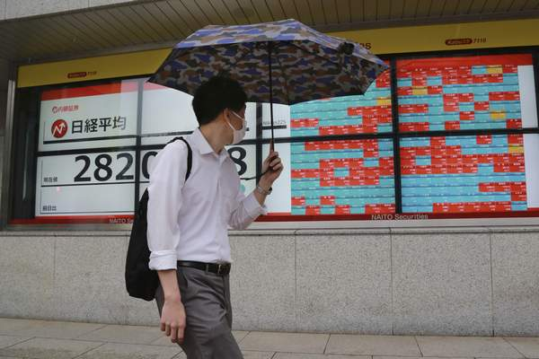 A man walks by an electronic stock board of a securities firm in Tokyo, Wednesday, Oct. 13, 2021. (AP Photo/Koji Sasahara)