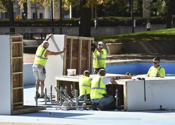 Katie Fyfe | The Journal Gazette City Parks Department crews clean and cover the fountains for the year at Freimann Square on Wednesday.