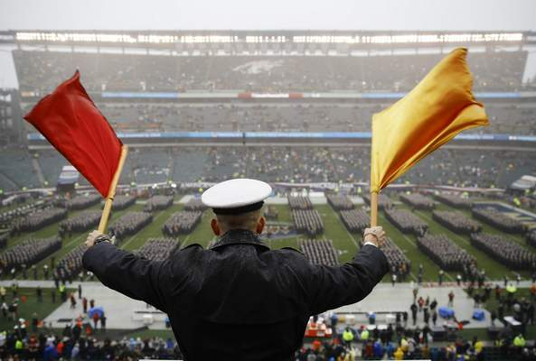 FILE - A Navy Midshipman signals his classmate on the field ahead of an NCAA college football game against Army in Philadelphia, in this Saturday, Dec. 14, 2019, file photo. Bump Army-Navy or go head-to-head with NFL? That's the choice facing those in charge with expanding the College Football Playoff if they want to take the format from four to 12 teams (AP Photo/Matt Rourke, File)