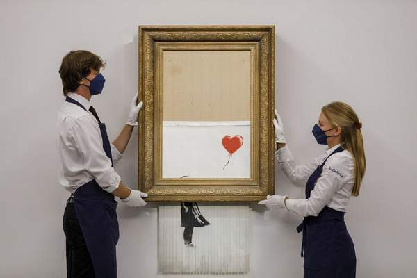 In this handout photo provided by Sotheby's Auction House, the auction for Banksy's Love is the Bin takes place in London, Thursday, Oct. 14, 2021. (Sotheby's Auction House via AP)