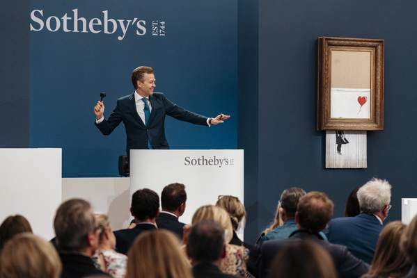 In this handout photo provided by Sotheby's Auction House, the auction for Banksy's Love is the Bin takes place in London, Thursday, Oct. 14, 2021. (Haydon Perrior/Sotheby's Auction House via AP)