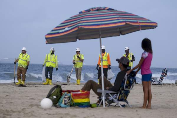 FILE - In this Monday, Oct. 11, 2021, file photo, workers in protective suits continue to clean the contaminated beach in Huntington Beach, Calif. (AP Photo/Ringo H.W. Chiu, File)