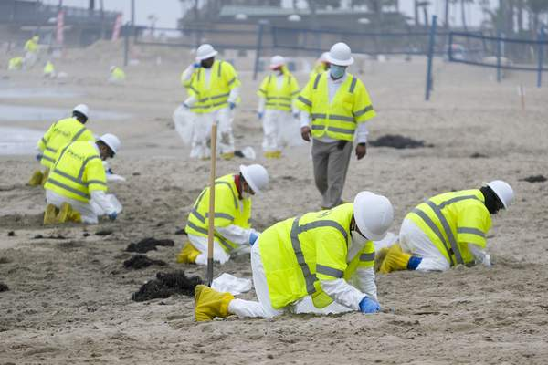 FILE - In this Thursday, Oct. 7, 2021, file photo, workers in protective suits clean the contaminated beach in Corona Del Mar in Newport Beach, Calif. (AP Photo/Ringo H.W. Chiu, File)