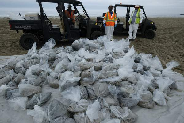 FILE - In this Thursday, Oct. 7, 2021, file photo, bags of crude oil collected by workers stack on a beach after an oil spill in Newport Beach, Calif. (AP Photo/Ringo H.W. Chiu, File)