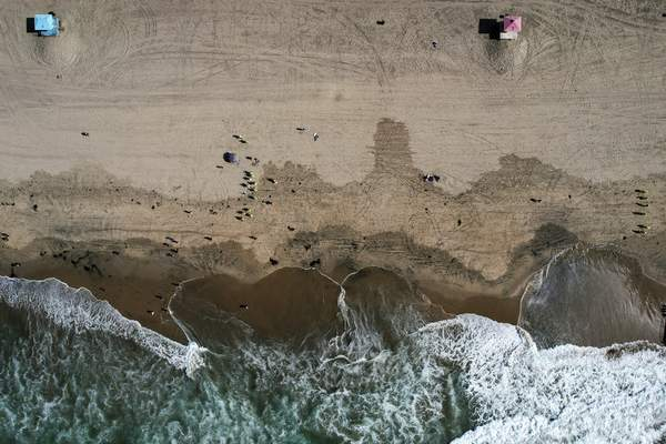 FILE - This Monday, Oct. 11, 2021, aerial file photo taken with a drone, shows beachgoers as workers in protective suits continue to clean the contaminated beach in Huntington Beach, Calif. (AP Photo/Ringo H.W. Chiu, File)