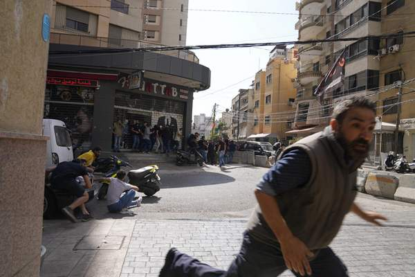 A man runs to take cover as supporters of a Shiite group allied with Hezbollah fire weapons during armed clashes that erupted during a protest in the southern Beirut suburb of Dahiyeh, Lebanon, Thursday, Oct. 14, 2021. It was not immediately clear what triggered the gunfire, but tensions were high along a former civil war front-line between Muslim Shiite and Christian areas. (AP Photo/Hassan Ammar)