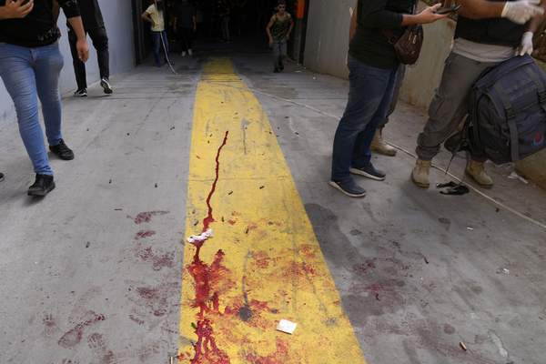 Supporters of a Shiite group allied with Hezbollah stand next to blood from an injured comrade during armed clashes that erupted during a protest in the southern Beirut suburb of Dahiyeh, Lebanon, Thursday, Oct. 14, 2021. It was not immediately clear what triggered the gunfire, but tensions were high along a former civil war front-line between Muslim Shiite and Christian areas. (AP Photo/Hassan Ammar)
