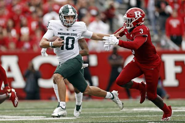 Michigan State quarterback Payton Thorne (10) runs away from Rutgers linebacker Olakunle Fatukasi (3) during the second half of an NCAA college football game Saturday, Oct. 9, 2021, in Piscataway, N.J. Michigan State won 31-13. (AP Photo/Adam Hunger)