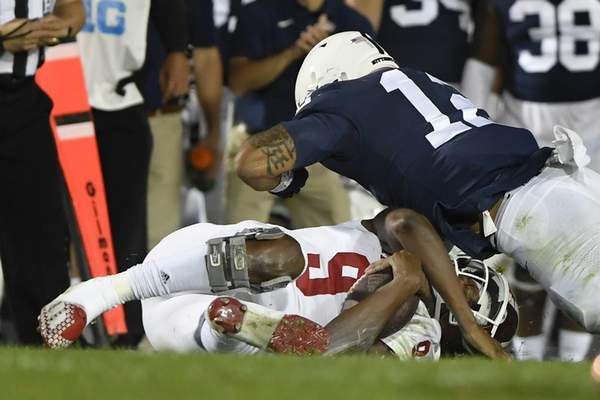 Penn State linebacker Brandon Smith (12) tackles Indiana quarterback Michael Penix Jr. (9) in the second half of their NCAA college football game in State College, Pa., on Saturday, Oct. 2, 2021. Penix was injured on the play and left the game.Penn State defeated Indiana 24-0. (AP Photo/Barry Reeger)