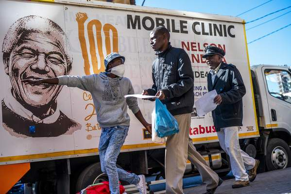 FILE - In this April 30, 2020 file photo, a volunteer directs two men towards a medical tent where they will be tested for COVID-19 as well as HIV and Tuberculosis, in downtown Johannesburg. (AP Photo/Jerome Delay, file)