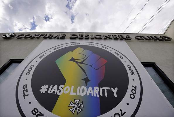 A poster advocating union solidarity hangs from a Costume Designers Guild office building, Monday, Oct. 4, 2021, in Burbank, Calif. (AP Photo/Chris Pizzello)
