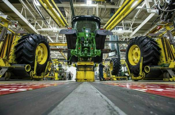 FILE - In this April 9, 2019, wheels are attach as workers assemble a tractor at John Deere's Waterloo, Iowa assembly plant. (Zach Boyden-Holmes/Telegraph Herald via AP, File)