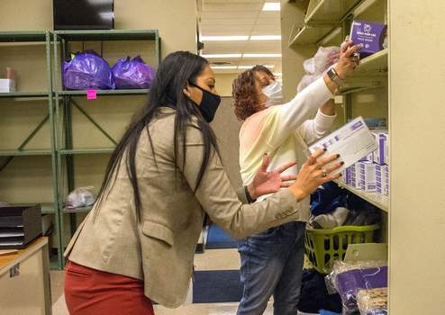 Michelle Davies | The Journal GazetteChristian Perez, front, family and transitions coordinator, and Suzy Smith, clothing bank assistant, both with Fort Wayne Community Schools, work to stock masks that were donated by the Fort Wayne Kiwanis Foundation Downtown Club.