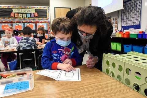 Michelle Davies   The Journal Gazette Principal for the Day, Dixie Garner, helps kindergartener Carter Knowle with a phonics lesson Thursday morning at South Wayne Elementary.
