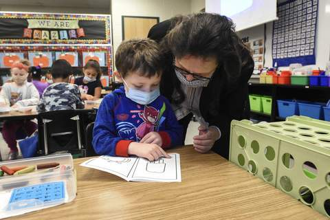 Michelle Davies   The Journal Gazette Serving as principal for the day, Dixie Garner helps kindergartner Carter Knowle with a phonics lesson Thursday morning at South Wayne Elementary School.
