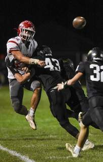 Katie Fyfe | The Journal Gazette  Adams Central senior Blake Heyerly gets tackled as he makes a pass during the second quarter against Churubusco at Churubusco High School on Friday.