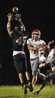 Katie Fyfe   The Journal Gazette Adams Central junior Ryan Black throws a pass over the outstretched arms of Churubusco senior Nick Nondorf in the second quarter Friday at Churubusco.