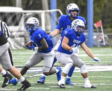 Michelle Davies | The Journal Gazette  Saint Francis' Cameron Peterson runs the ball in the first half of Saturday's game against Indiana Wesleyan at Bishop D'Arcy Stadium.