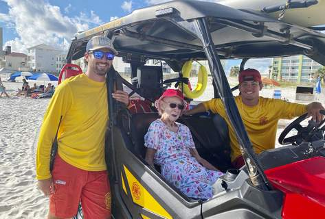 Exchange-95 Year Old-Beach Trip Associated Press: In this image provided by Kimberly Waterbury, Dottie Schneider, 95, poses with Orange Beach Surf Rescue lifeguards in Orange Beach, Ala. (Kimberly WaterburyHONS)