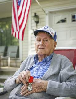 Mike Moore | The Journal Gazette 97-year-old WWII veteran Norvin McClure holds the French Legion of Honour medal at his home during a portrait session. Norvin will be awarded the medal in Mississippi next month for his service during World War II.