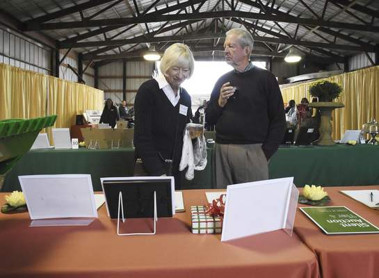 Rachel Von | The Journal Gazette  Karen Surguine, board member of the Little River Wetlands Project, and her husband Art look at silent auction items at Eagle Marsh barn where the Frogapalooza event was held on Saturday September 29th, 2018. The event included short hikes, drinks, dinner, bidding on auction items, and a bonfire.