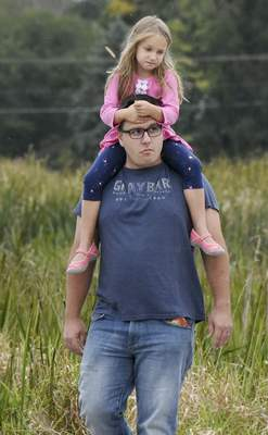Rachel Von | The Journal Gazette Mike Taylor carries his daughter Eliana, 5, on his shoulders on the trail leading up to the Eagle Marsh barn where Frogapalooza was held Saturday.