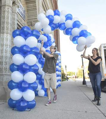 Michelle Davies | The Journal Gazette Thane Madeford and Tori VanDiepenbos, both from A Party Apart, set up balloon arches Friday morning at the  University of Saint Francis downtown for Welcome Weekend. The fall semester begins Monday.