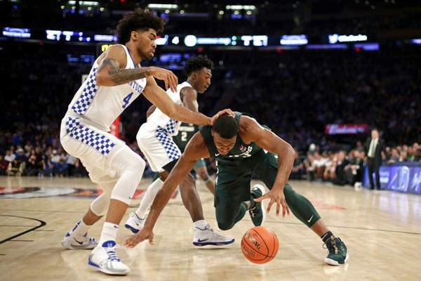 Adam Hunger | Associated Press Michigan forward Xavier Tillman (23) falls to the court in front of Kentucky forward Nick Richards (4) during the first half of an NCAA college basketball game Tuesday in New York.