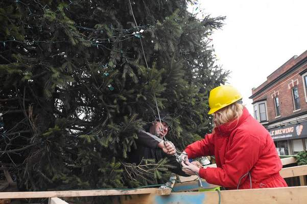 Michelle Davies | The Journal Gazette Felisha Anderson and Jay Kleber reattach guy wires to the Christmas on Broadway tree Friday.