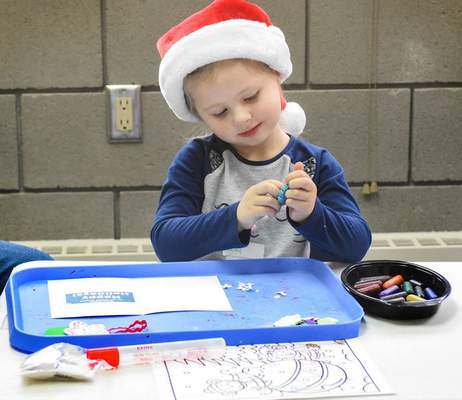Michelle Davies | The Journal Gazette Ruby Reche, 3, of Fort Wayne works on making a holiday card at Friday morning's Holiday Fun class at the Fort Wayne Parks and Recreation Community Center.