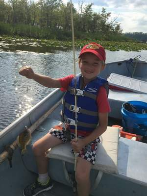 "Tom ""Bearcat"" Quigley IV, 5, of Fort Wayne proudly displays his first bluegill caught from a boat while fishing on Lake Tippecanoe in August with his father, Brian ""Bear"" Quigley."