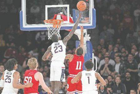 Associated Press Connecticut forward Akok Akok blocks Indiana guard Devonte Green's shot during Tuesday night's Jimmy V Classic game in New York.
