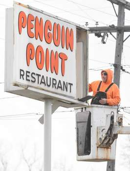 Michelle Davies   The Journal Gazette Bob Hershman, a sign installer with Indiana Signworks, works on the Penguin Point sign along Winchester Road on Friday morning.