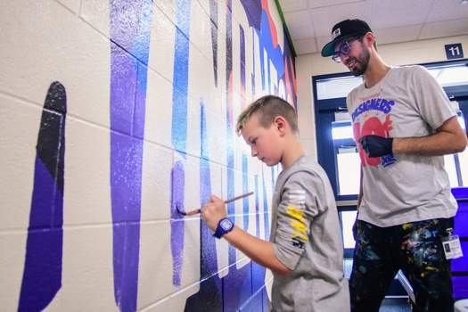 """Mike Moore   The Journal Gazette Fourth grader Jacob Schlotterback lends a hand painting a  mural  with local artist Matt Plett at Cedar Canyon Elementary School on Friday. The mural reads, """"Choose Kindness."""""""