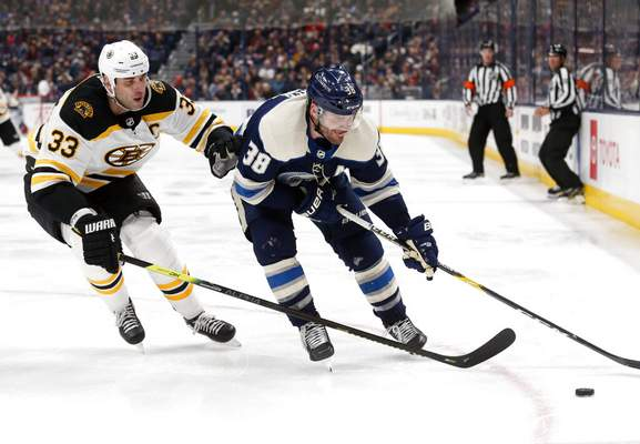 Paul Vernon | Associated PressColumbus Blue Jackets forward Boone Jenner, right, chases the puck in front of Boston Bruins defenseman Zdeno Chara, of Slovakia, during the second period an NHL hockey game in Columbus, Ohio, Tuesday.