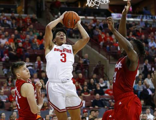 Jay LaPrete | Associated PressOhio State's D.J. Carton, center, shoots between Nebraska's Thorir Thorbjarnarson, left, and Yvan Ouedraogo during the second half of an NCAA college basketball game Tuesday, in Columbus, Ohio. Ohio State defeated Nebraska 80-68.