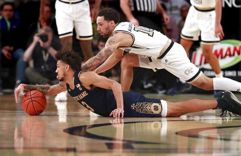 Curtis Compton/Atlanta Journal-Constitution | Associated PressNotre Dame guard Prentiss Hubb, left, and Georgia Tech guard Jose Alvarado dive for the ball during the first half of an NCAA college basketball game Wednesday, in Atlanta.