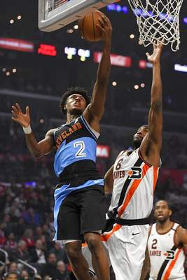 Mark J. Terrill | Associated PressCleveland Cavaliers guard Collin Sexton, left, shoots as Los Angeles Clippers forward Maurice Harkless, center, defends while forward Kawhi Leonard watches during the first half of an NBA basketball game Tuesday, in Los Angeles.