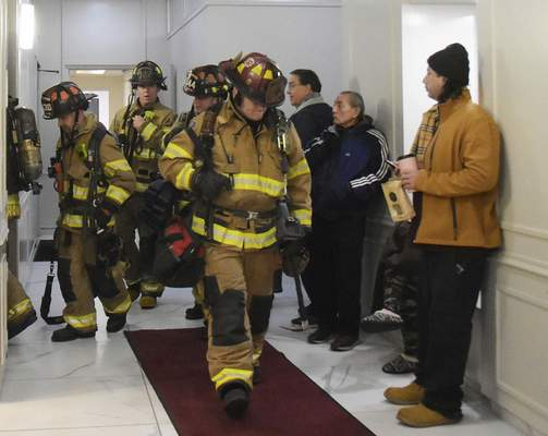 Residents wait as firefighters come through the lobby after Wednesday's blaze at Three Rivers Apartments.
