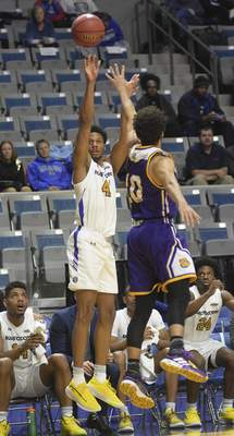 Katie Fyfe | The Journal Gazette  Purdue Fort Wayneguard Marcus Deberry takes a shot while Western Illinois guard Kobe Webster defends him during the second half at Memorial Coliseum.