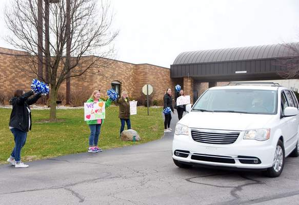 Katie Fyfe | The Journal Gazette Concordia Lutheran School and preschool staff members, from left, Lynn Koenig,  Roxann Wert,  Bonnie Hoffschneider,  Abby Slaten and  Dawn Slaten cheer on parents and students Wednesday as they pick up their week's worth of lunch and breakfast packaged in Grab 'N Go Meals . Schools across the area have been distributing meals during the cancellation of school due to the coronavirus pandemic.