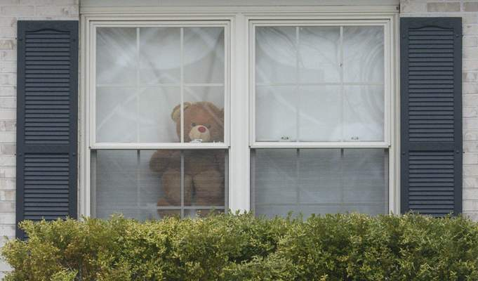 Michelle Davies | The Journal Gazette A teddy bear takes a peek outside from the window of his home, waiting to be spotted by kids as part of a scavenger hunt.