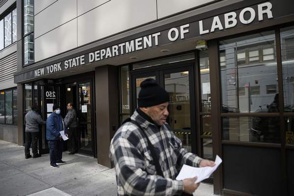 In this March 18, 2020 file photo, visitors to the Department of Labor are turned away at the door by personnel due to closures over coronavirus concerns in New York. (AP Photo/John Minchillo, File)