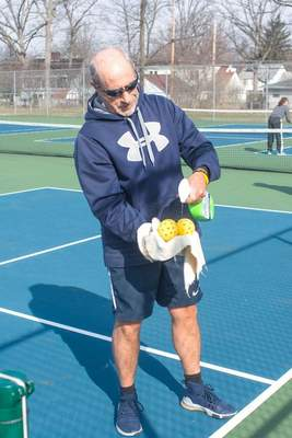 Michelle Davies | The Journal Gazette Steve Matthews of Fort Wayne sprays down whiffle balls with bleach water after playing pickleball Thursday morning at Lions Park.