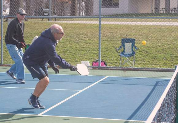Michelle Davies | The Journal Gazette Wearing gloves and staying a safe distance apart, pickleball partners Bruce Hartman, of Leo, rear, and Steve Matthews, of Fort Wayne, front, play pickleball Thursday morning at Lions Park.