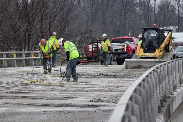 Mike Moore | The Journal Gazette Construction workers from R.L. McCoy Inc. of Columbia City use jackhammers Friday while working on the Halter Road bridge near Leo-Cedarville.