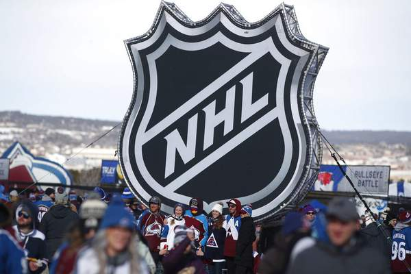 David Zalubowski, File | Associated PressFILE - In this Saturday, file photo, fans pose below the NHL league logo at a display outside Falcon Stadium before an NHL Stadium Series outdoor hockey game between the Los Angeles Kings and Colorado Avalanche, at Air Force Academy, Colo. The NHL Players' Association's executive board is voting on a 24-team playoff proposal as the return-to-play format, a person with knowledge of the situation told The Associated Press, late Thursday.