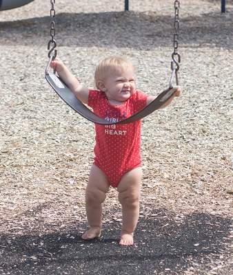 Michelle Davies | The Journal Gazette Eleven-month-old Pippa Stuckwisch of South Bend enjoys a stop at Hamilton Park's playground while on a visit with friends Friday morning.