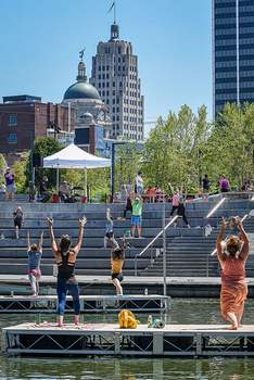 Mike Moore | The Journal Gazette  River, Set, Go! visitors perform yoga moves on the Promenade Park Amphitheatre steps Saturday with instructors floating on the St. Marys River.